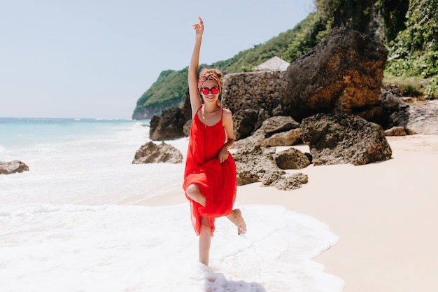 Joyful young woman standing on one leg at ocean coast and waving hand. outdoor portrait of beautiful caucasian girl in red dress expressing happiness at wild beach.