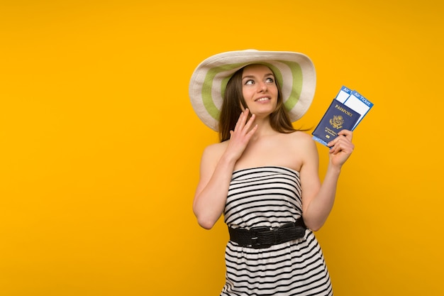 Joyful young woman in a straw hat and a striped dress is holding airline tickets with a passport on a yellow background.