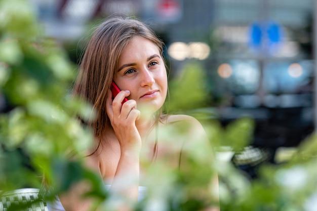 屋外のストリートカフェに座ってスマートフォンで話しているうれしそうな若い女性