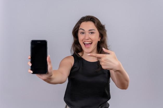 Gioiosa giovane donna che indossa la maglietta nera ha tenuto il telefono per inoltrare e indicare il telefono sul muro bianco