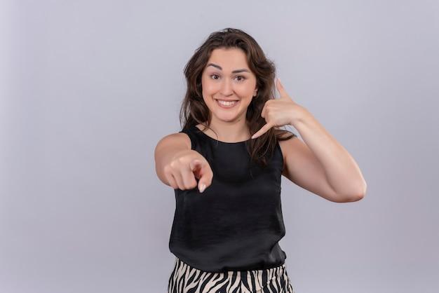 검은 땀받이를 입고 즐거운 젊은 여자가 전화를 보여주고 흰 벽에 그녀의 손가락을 가리 킵니다.