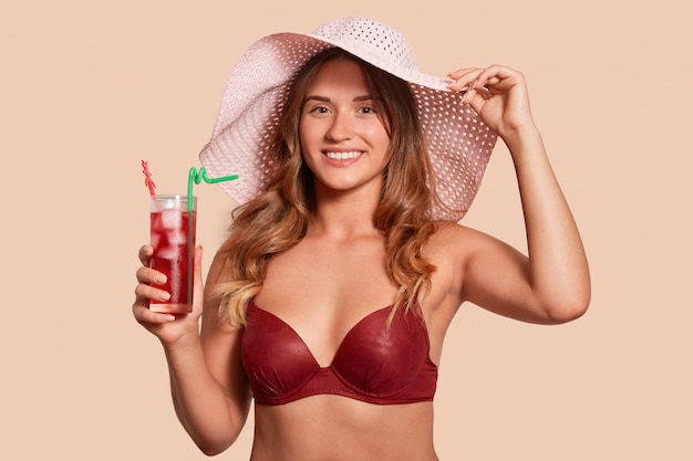 Joyful young woman wearing red swimsuit and straw hat, enjoying sweet taste of cocktail, holds glass in hand, keeps other hand on hat, expresses gladness, model posing isolated on studio wall.