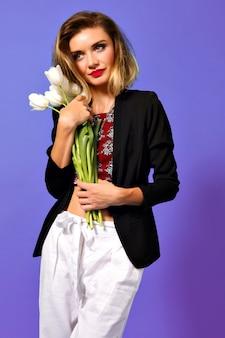 紫色の背景で隔離の側に微笑んで白いチューリップの花束を持つうれしそうな若い女性。