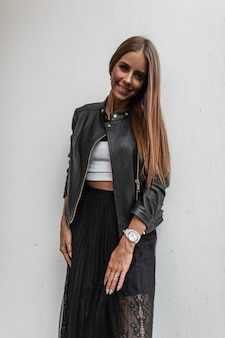 도시에있는 흰색 건물 근처에 포즈를 취하는 트렌디 한 블랙 스커트에 우아함 화이트 탑에 세련된 가죽 재킷에 귀여운 미소로 갈색 머리를 가진 즐거운 젊은 여자. 꽤 행복한 여자 모델 야외