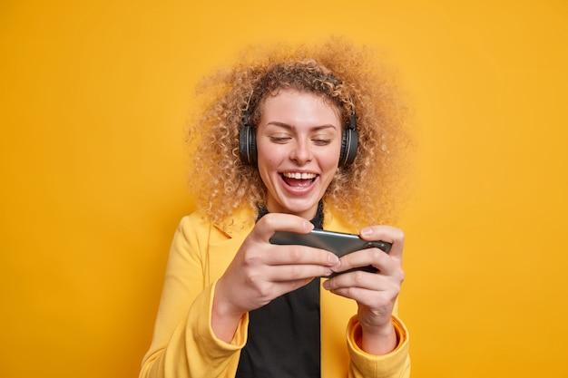 Радостная молодая женщина с вьющимися волосами держит смартфон горизонтально, играет в видеоигры, пытается пройти сложный уровень, использует беспроводные наушники, изолированные на желтой стене. технологическая зависимость