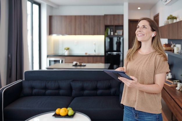 Радостная молодая женщина с цифровым планшетом, использующая приложение умного дома для контроля температуры кондиционера