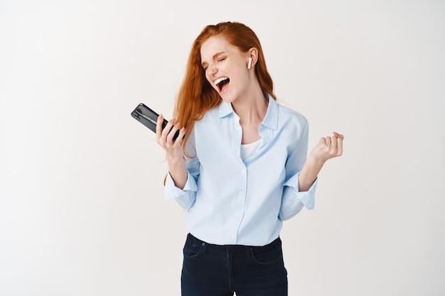 긴 빨간 머리를 가진 즐거운 젊은 여성이 무선 헤드폰으로 노래를 부르고 음악을 듣고, 즐겁게 놀고, 스마트폰을 들고, 흰 벽 위에 서 있습니다.