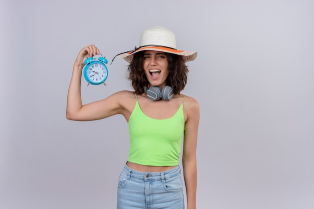 A joyful young woman with short hair in green crop top wearing sun hat holding blue alarm clock on a white background
