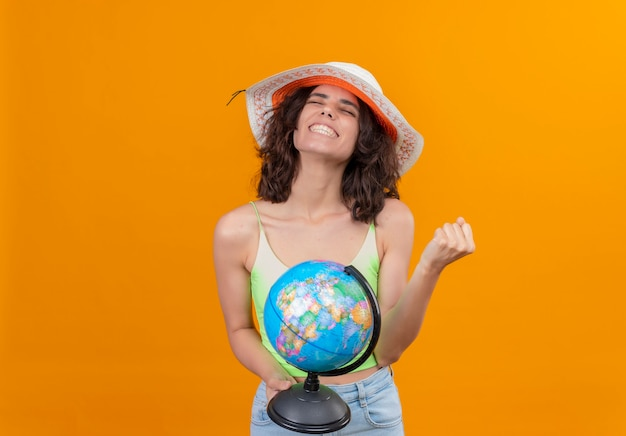 A joyful young woman with short hair in green crop top wearing sun hat holding a globe with clenched fist