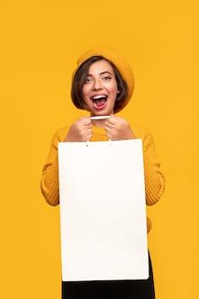 白い買い物袋を持つうれしそうな若い女性