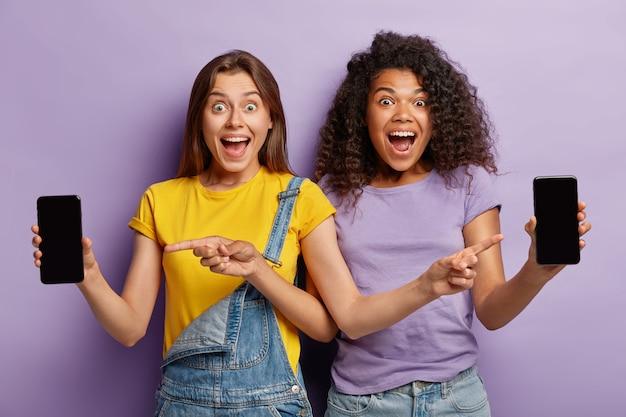 うれしそうな若い女性がスマートフォンのディスプレイ画面を指差す