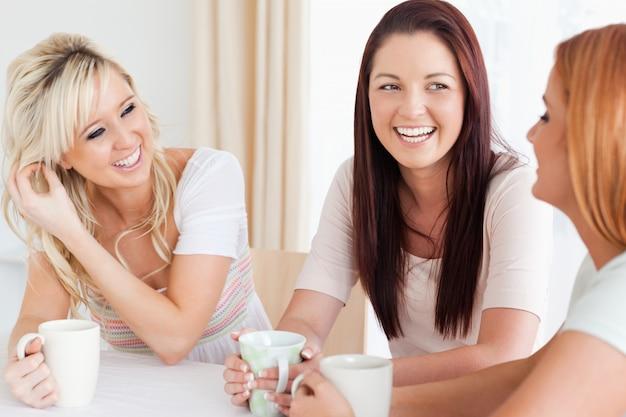 カップでテーブルに座っている楽しい若い女性