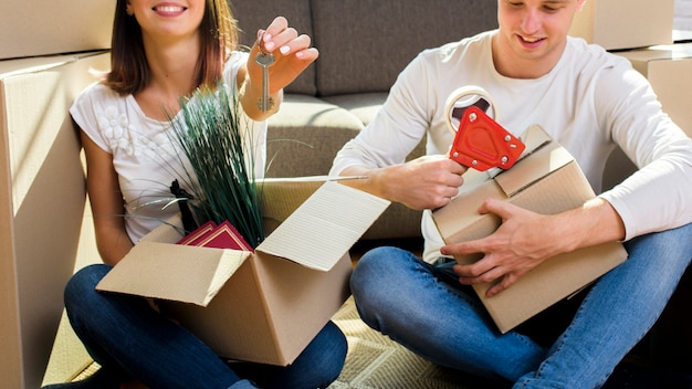 Joyfull couple packing things in cardboard boxes