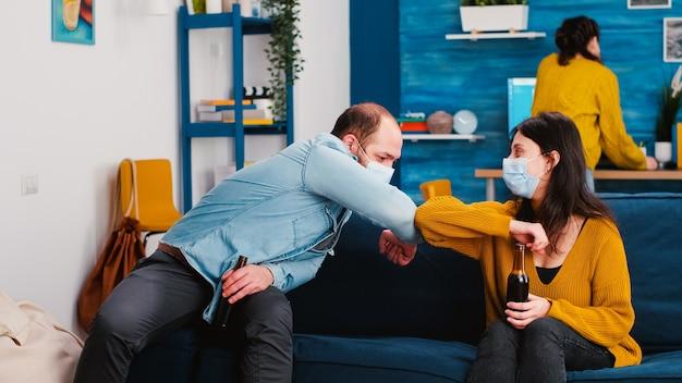 새로운 일반 파티에서 거실 소파에 앉아 즐거운 친구들이 코로나 바이러스 확산을 피하는 새로운 인사 팔꿈치 충돌