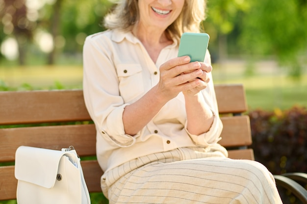 Joyfully smiling woman with smartphone in hands