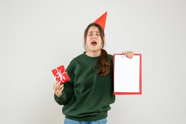 Joyless girl with party cap crying while holding documents and gift on white