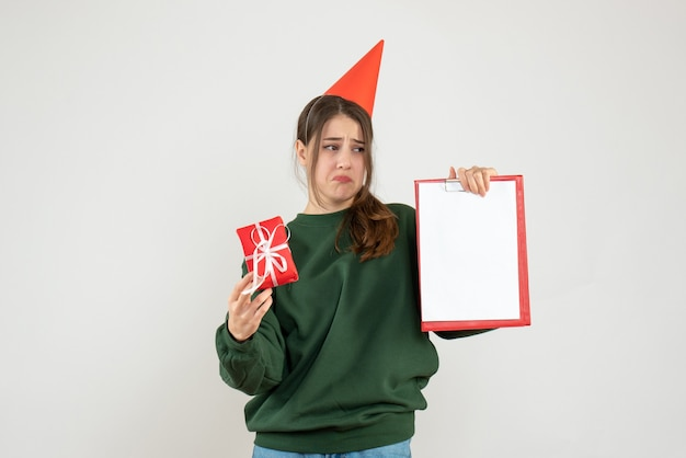 Joyless girl with party cap looking at her document on white