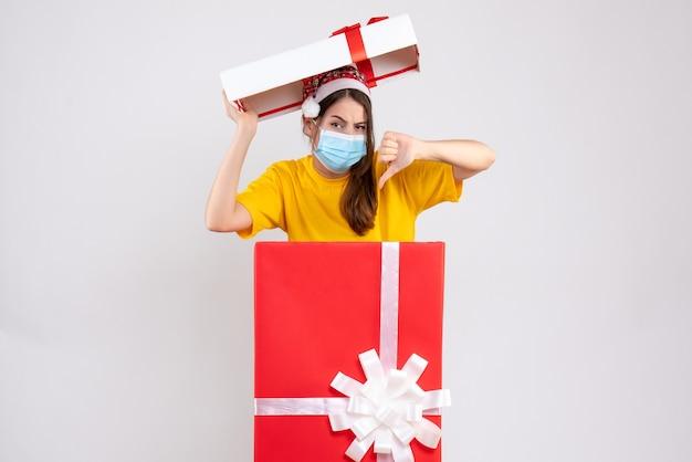 白の大きなクリスマスプレゼントの後ろに立って親指ダウンサインを作るサンタ帽子と喜びのない女の子