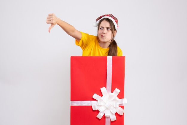 Joyless girl with santa hat making thumb down sign standing behind big xmas gift on white