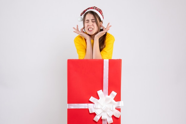 Joyless girl with santa hat standing behind big xmas gift on white