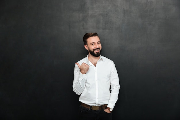 Joyous adult guy in office posing on camera, gesturing with thumb aside over dark gray copy space