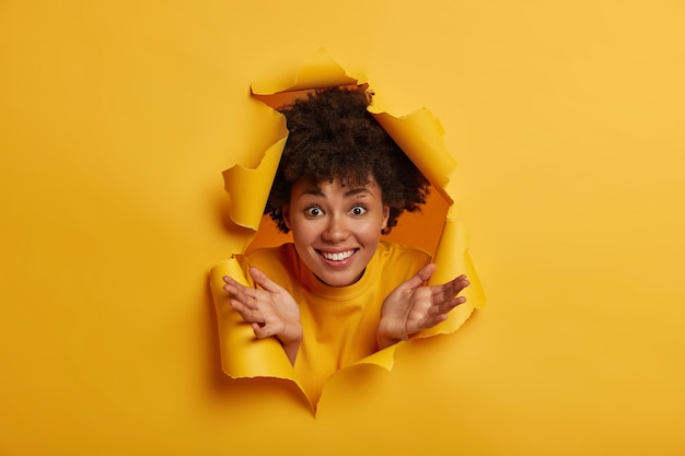 Joyous afro american woman in yellow sweater, spreads palms, shows white teeth, has fun indoor, looks through torn paper hole background