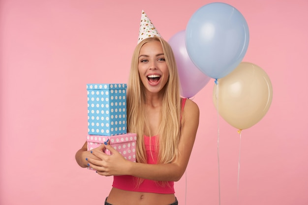 ピンクのトップとホリデーキャップの楽しい魅力的な若い長い髪の女性は、色とりどりの気球でピンクの背景の上にポーズをとって、誕生日プレゼントを手に入れて興奮して驚いています