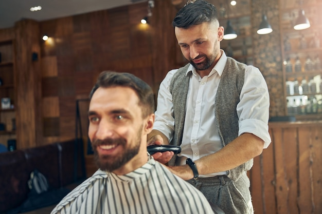 Joyous barber using electric hair trimmer to cut hair of his smiley client