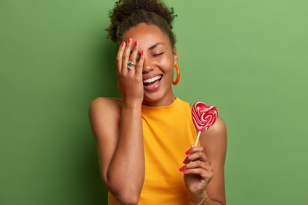 Joyous black girl makes face palm, smiles broadly, closes eyes, poses with heart lollipop on stick, has fun indoor, holds yummy candy, wears yellow t shirt, stands against green vivid wall