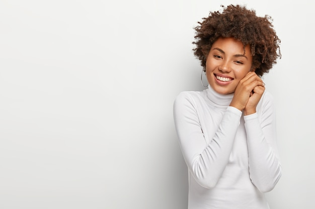 Joyous black woman with pleasant smile, keeps hands together near face, looks happily