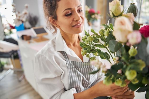 Радостная дама брюнетка любуясь цветочной композицией