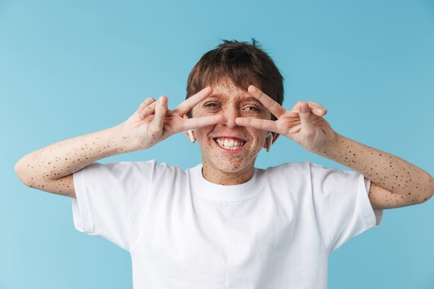 Of joyous caucasian boy  with freckles wearing white casual t-shirt and earpods showing peace sign isolated over blue wall