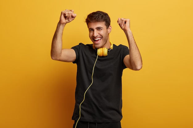 Joyous caucasian man listens new song, dances and moves in rhythm, raises arms with clenched fists, dressed in black clothing, wears headphones around neck