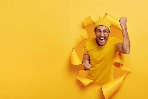 Joyous cheering man posing through torn paper
