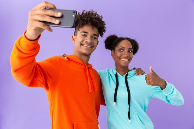 Joyous couple wearing colorful sweatshirts taking selfie on smartphone, isolated over violet wall