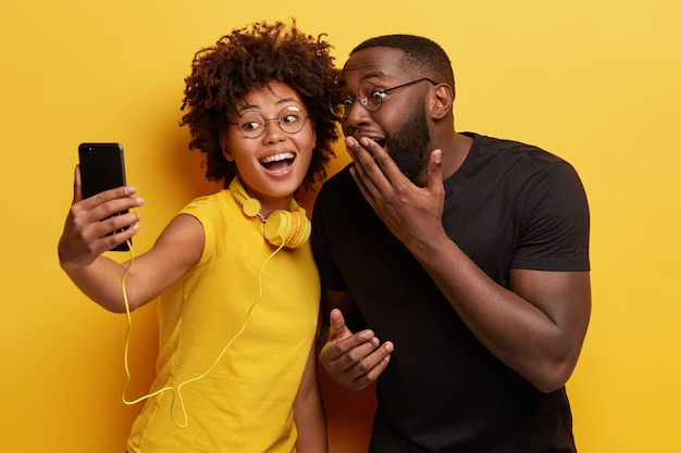 Joyous dark skinned female and male couple have fun together, pose for making selfie portrait