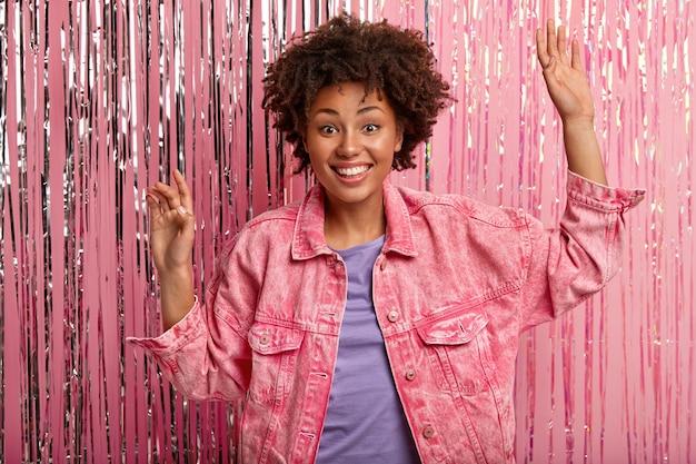 Il modello femminile dalla pelle scura gioiosa balla attivamente, ha un'espressione facciale sorpresa felice