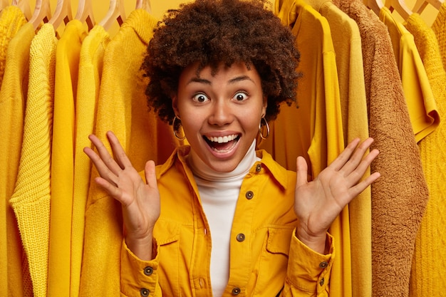 La donna riccia emotiva gioiosa allarga le palme, esclama con felicità, si oppone a abiti alla moda gialli su rack, si rallegra delle grandi vendite nel centro commerciale