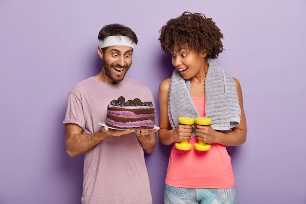 Joyous female and male stare with happiness and temptation at delicious cake, being hungry after exhausted workout, avoid eating sweet desserts with much calories, exercise with dumbbells in gym
