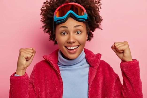 즐거운 여성 스노 보더가 승리로 주먹을 움켜 쥐고 특별한 스키 고글을 쓰고 따뜻한 빨간 재킷을 입고 활짝 웃으며 승리를 응원합니다