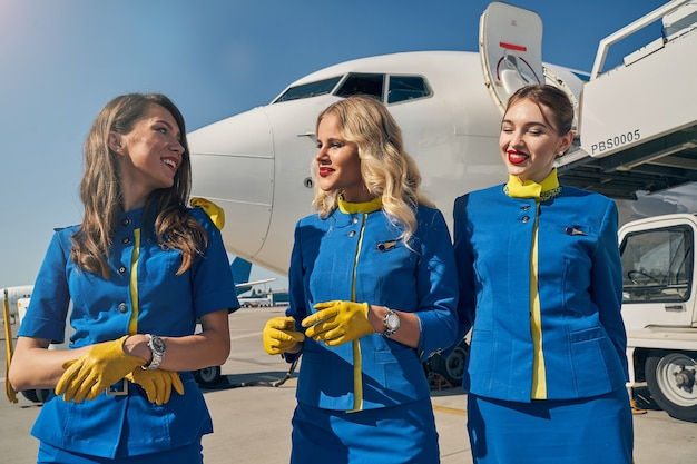Joyous flight attendant and her female colleagues standing at the airdrome