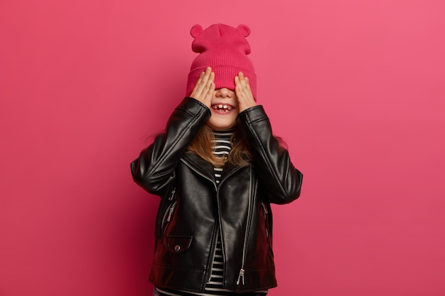 Joyous girl hides face with hat, holds palms on eyes, wears fashionable leather jacket, isolated on pink wall, has broad smile, plays hide and seek with friends, foolishes around in kindergarten