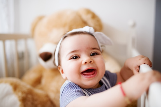 Joyous girl laughing and playing with her teddy bear.