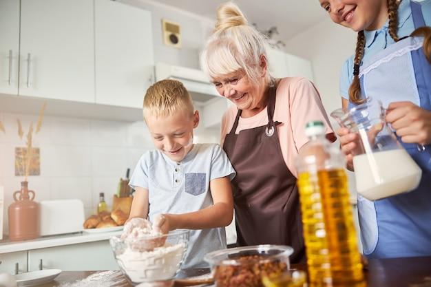 즐거운 할머니와 그녀의 손자들이 함께 요리