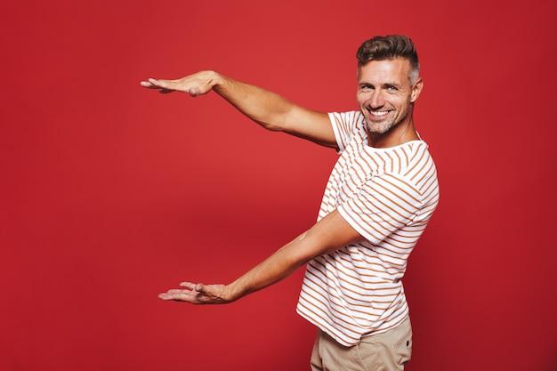 Радостный парень в полосатой футболке жестикулирует и демонстрирует размер с copyspace, изолированным на красном