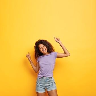 Радостная счастливая привлекательная темнокожая женщина с вьющимися волосами, поднимает руки под хорошую звуковую музыку, стройная фигура.