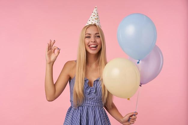 여러 가지 빛깔의 공기 풍선에서 포즈를 취하는 동안 기쁨의 축제 옷에 즐거운 긴 머리 금발 아가씨, 확인 기호에 접힌 손가락으로 분홍색 배경 위에 절연, 카메라에 웃고 혀를 보여주는