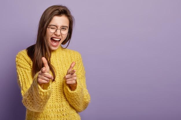 Gioiosa bella femmina sbatte le palpebre, esclama di felicità, ti indica, dimostra la sua scelta