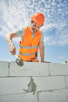 Радостный мужчина-строитель в каске с кирпичным молотком