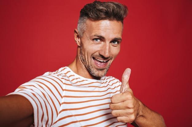 Радостный мужчина в полосатой футболке улыбается и показывает палец вверх, делая селфи, изолированное на красном